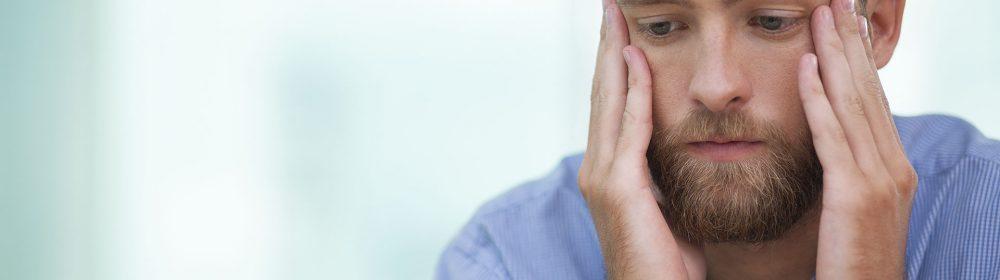 Homem com afeição de preocupado e com as mãos no rosto