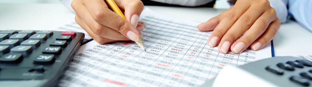 Mulher com calculadora e escrevendo em uma folha