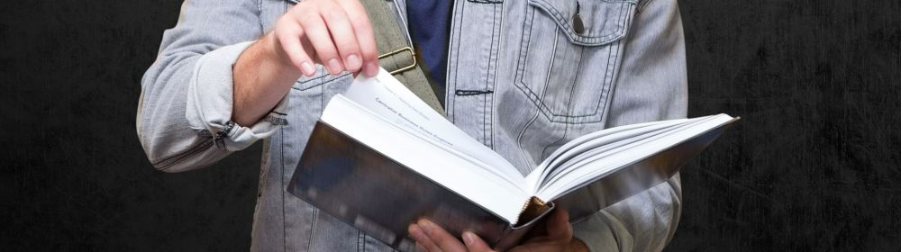 menino folhando um livro grosso